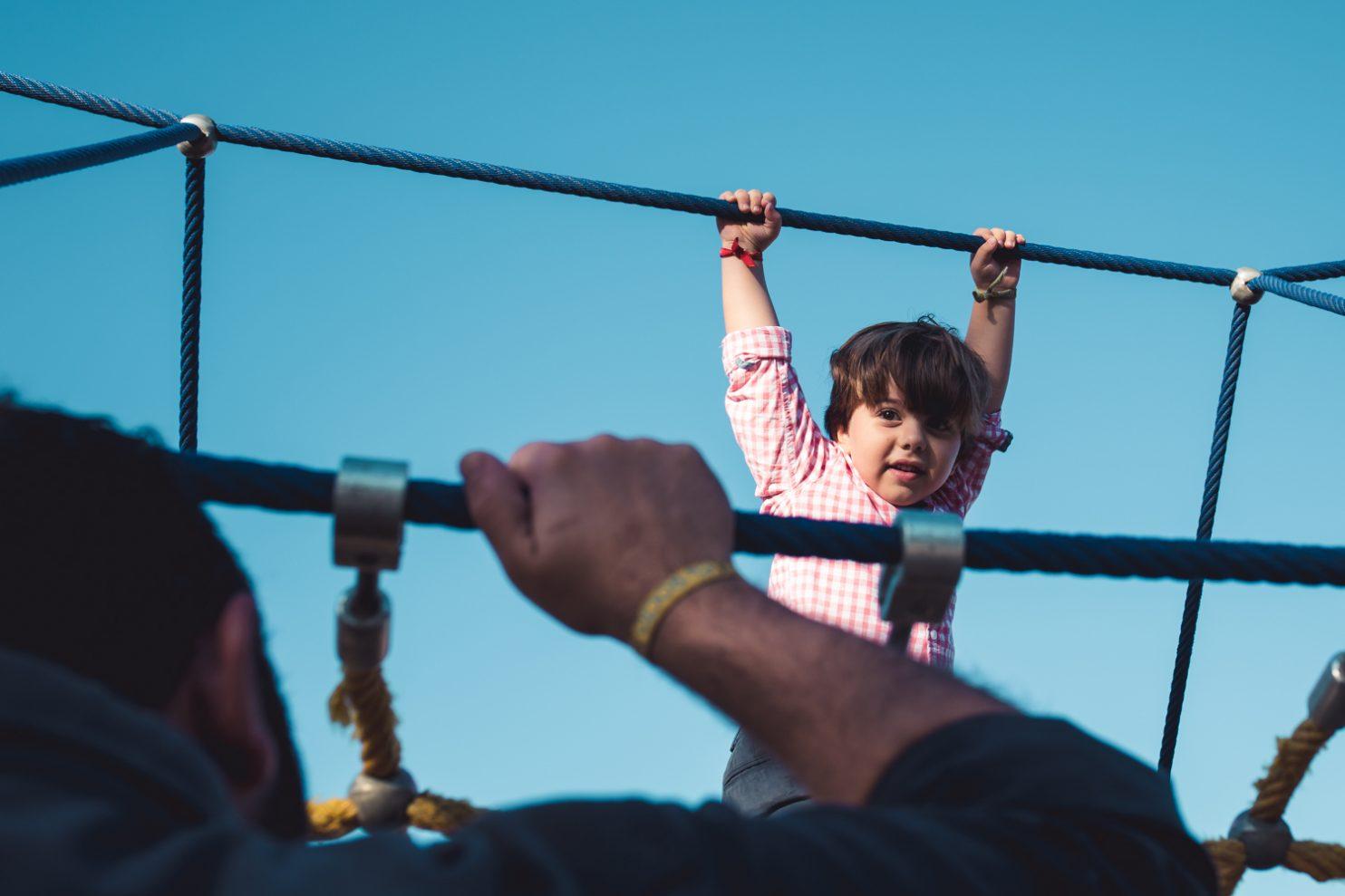 Niño jugando en un puente de cuerdas del parque infantil