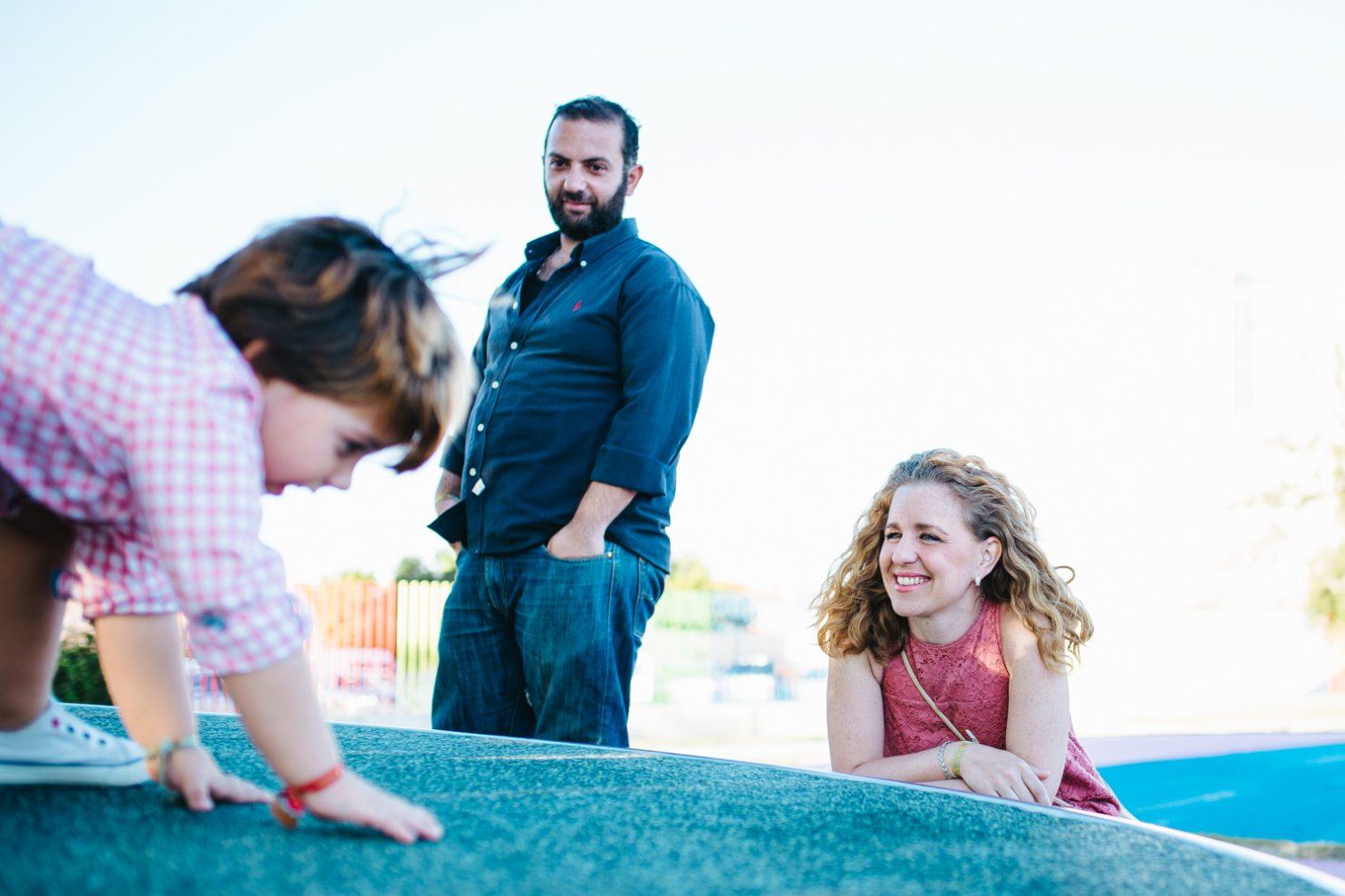 Niño jugando en un columpio de un parque infantil y sus padres lo observan jugar